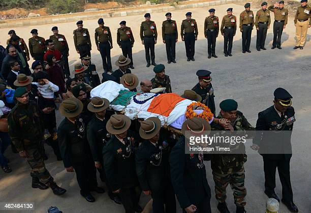 Son and daughter salutes as colleagues and senior army officials carry the mortal remains of martyred hero Colonel Munindra Nath Rai during cremation...