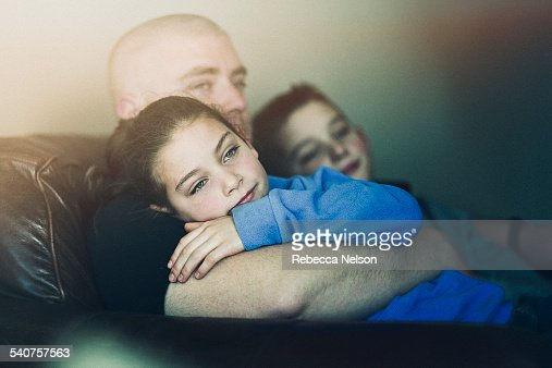 Son and daughter sitting on dad's lap