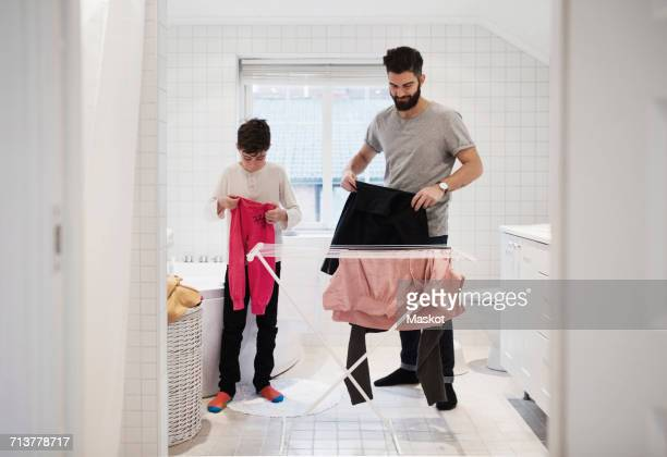 son and father drying clothes on rack at home - drying stock pictures, royalty-free photos & images
