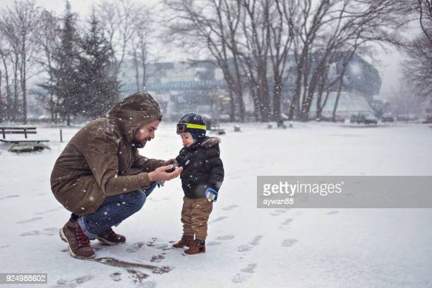 son and father enjoying beautiful winter - first occurrence stock pictures, royalty-free photos & images
