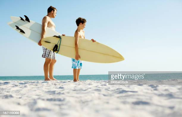 Son and father with surfboards standing on the beach