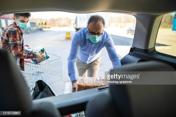 son and father with surgical masks packing groceries from supermarket in car trunk - car trunk stock pictures, royalty-free photos & images