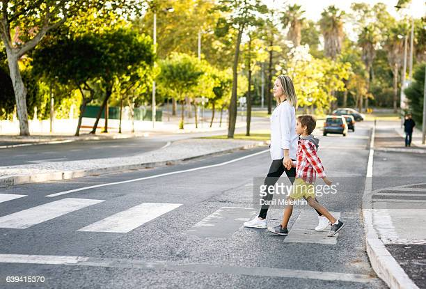 son and mom holding hands - pedestrian crossing stock photos and pictures