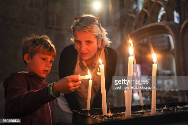 Son and mother lighting candle in church