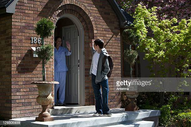 Son and Mother waving goodbye to each other at their front door as son leaves house