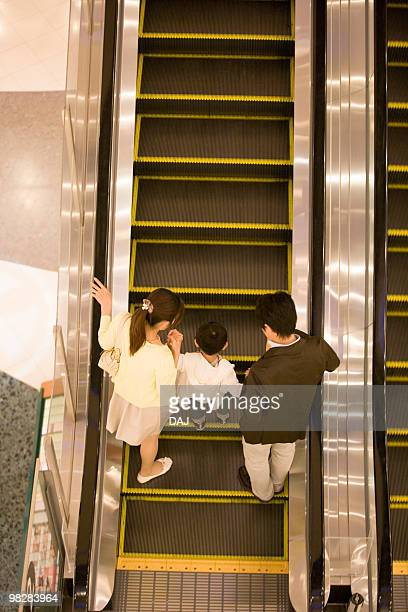 Son and Two Parent Ridding on Escalator in Department Store