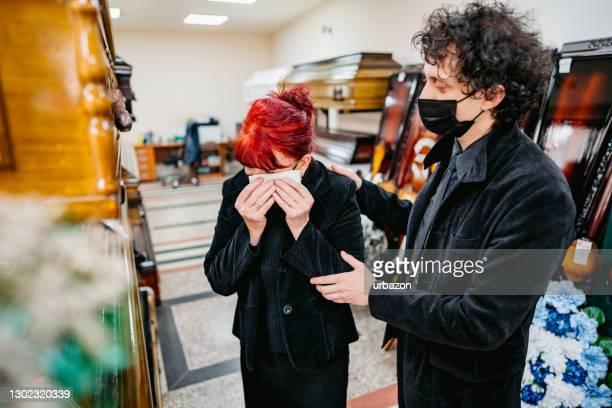 zoon troost zijn moeder in begrafenissalon - uitvaartcentrum stockfoto's en -beelden