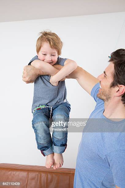 Son doing chin ups on fathers arm