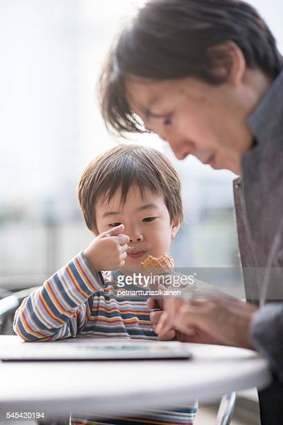 Son eating ice cream while father with tablet.
