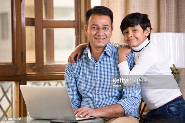 son embracing his father at home - son stock pictures, royalty-free photos & images