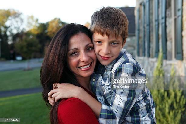 Son embracing mother, smiling, portrait