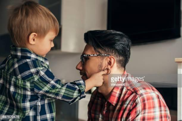 Son examining fathers flesh tunnel