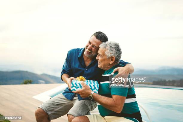 son giving a gift for his father on father's day. - fathers day stock pictures, royalty-free photos & images
