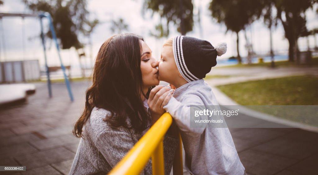 Sonen ger en kyss till sin mor på lekplatsen : Bildbanksbilder