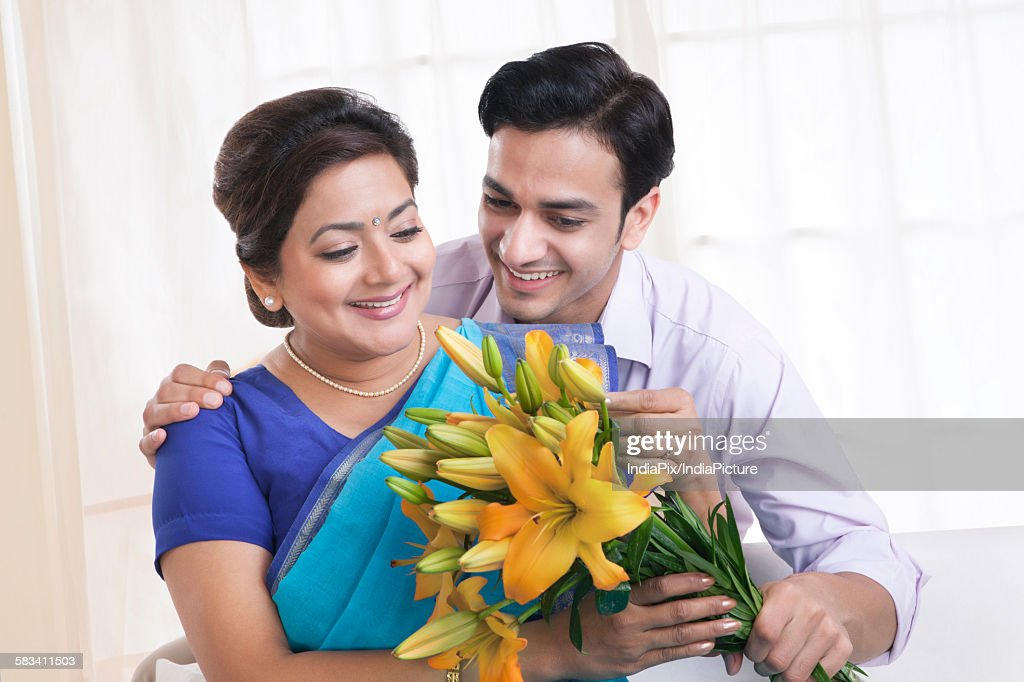 Son giving his mother flowers : Stock Photo