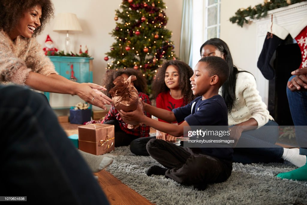 Son Giving Mother Gift As Multi Generation Family Celebrate Christmas At Home Together : Stock Photo