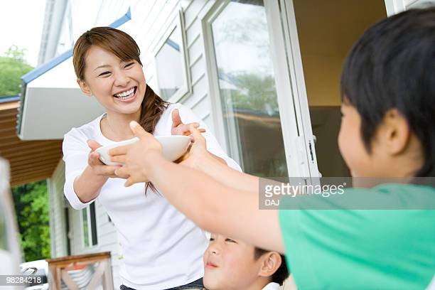 Son handing a bowl to mother