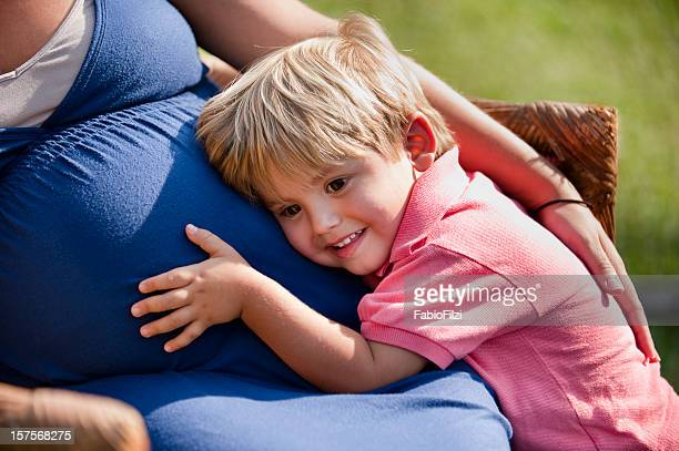 Son has his ear pressed against his mother's pregnant belly