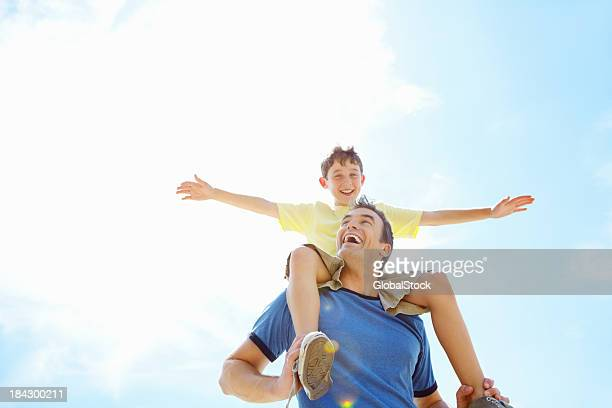 Son having fun sitting on his father's shoulders