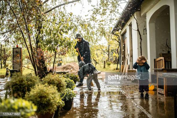 son helping father and sweeping water from front yard on rainy day - inondazione foto e immagini stock