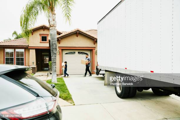Son helping father carry items in new home from moving truck