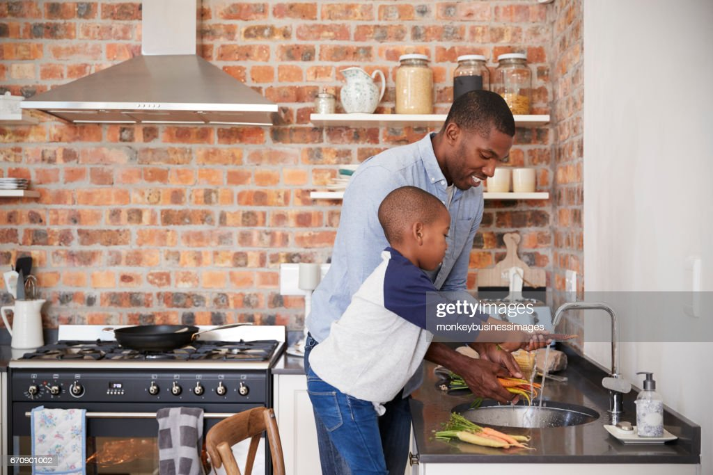 Son Helping Father To Prepare Vegetables For Meal In Kitchen : Stock Photo