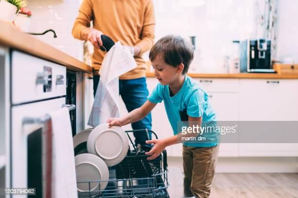 sohn hilft vater mit der spülmaschine. chores-konzept - haushaltsaufgabe stock-fotos und bilder