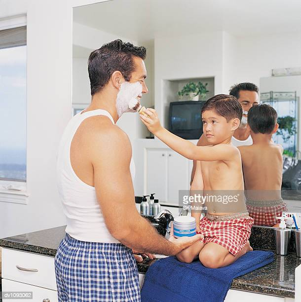 son helping his father shave in the bathroom - shorts stock pictures, royalty-free photos & images