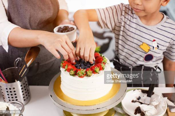Son helping mother putting cake toppings