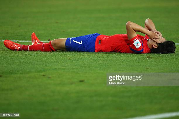 Son Heung Min of Korea Republic lies on the ground dejected after defeat during the 2015 Asian Cup final match between Korea Republic and the...