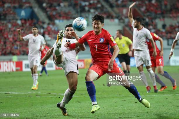 Son Heung Min of South Korea and Alireza Jahan Bakhsh of Iran compete for the ball during the FIFA World Cup Russia Asian qualifier match between...