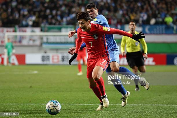 Son Heung Min of South Korea and Javokhir Sokhibov of Uzbekistan compete for the ball during the 2018 FIFA World Cup qualifying match between South...