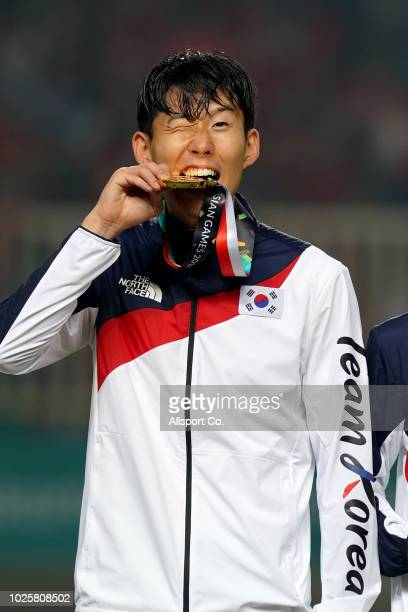 Son Heung Min of South Korea bites his gold medal after defeating Japan 2-1 in extra time during the Men's Football gold medal match between South...