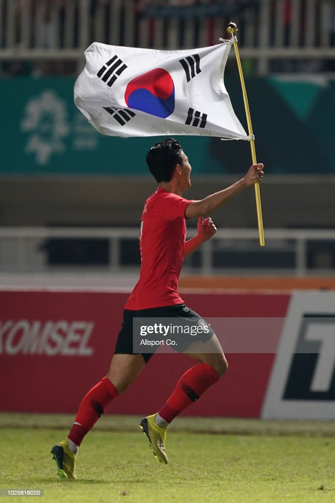Son Heung Min of South Korea celebrates with a flag after defeating Japan 2-1 in extra time during the Men's Football gold medal match between South Korea and Japan at the Pakan Sari Stadium on day fourteen of the 18th Asian Games on September 1, 2018 in Jakarta, Indonesia.