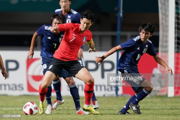 Son Heung Min of South Korea competes for the ball during the Men's Football gold medal match between South Korea and Japan at the Pakan Sari Stadium...
