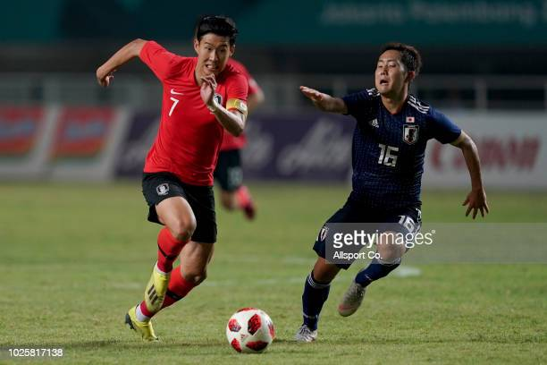 Son Heung Min of South Korea competes for the fall with Watanabe Kouta of Japan during the Men's Football gold medal match between South Korea and...