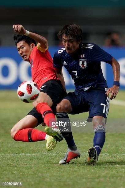 Son Heung Min of South Korea competes with Hara Teruki of Japan during the Men's Football gold medal match between South Korea and Japan at the Pakan...