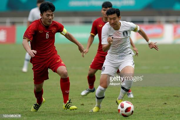 Son Heung Min of South Korea holds off Luong Xuan Truong of Vietnam during the Men's Footbal semi final competition between Vietnam and South Korea...