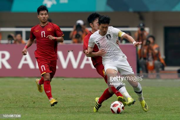 Son Heung Min of South Korea is held during the Men's Footbal semi final competition between Vietnam and South Korea held at the Pakan Sari Stadium...