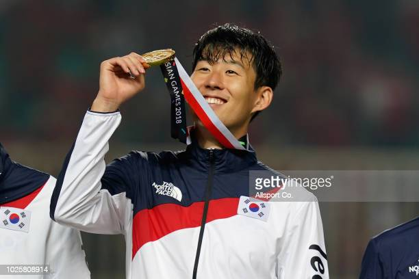 Son Heung Min of South Korea rises his gold medal after defeating Japan 21 in extra time during the Men's Football gold medal match between South...