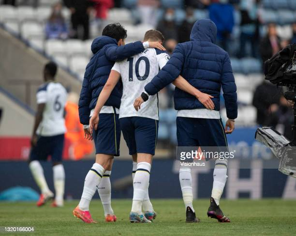 Son Heung-Min and Dele Alli of Tottenham Hotspur walk off with their arms around team mate Harry Kane at the final whistle after the Premier League...
