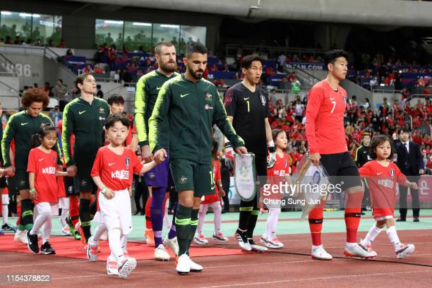 Son Heungmin of South Korea and Aziz Behich of Australia lead the teams entering the pitch prior to the international friendly match between South...