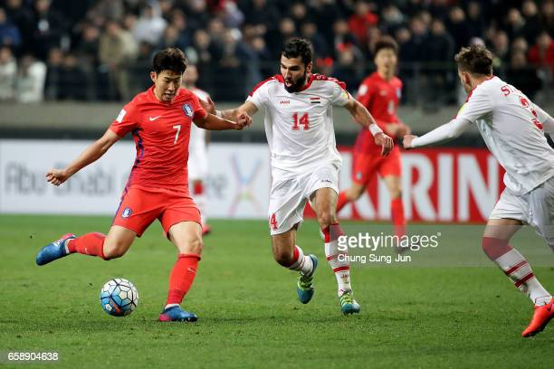 Son HeungMin of South Korea competes for the ball with Hag Mohamad Tamer of Syria during the FIFA World Cup Qualification AFC Final Group Stage match...