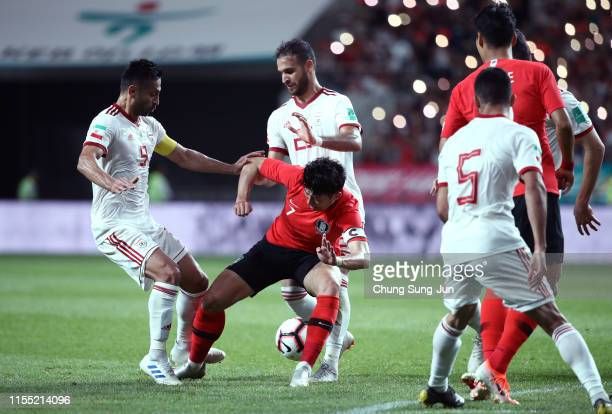 Son HeungMin of South Korea competes for the ball with Omid Ebrahimi Zarandini and Aliahyar Sayyadmanesh of Iran during the international friendly...