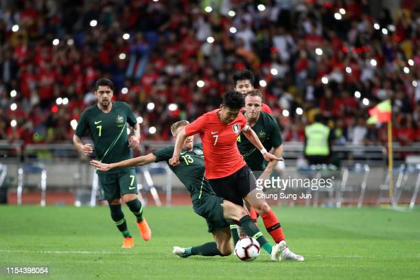Son Heungmin of South Korea is tackled by James Jeggo of Australia during the international friendly match between South Korea and Australia at Busan...
