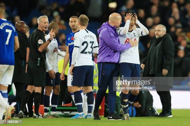 Son HeungMin of Spurs is consoled following his foul on Andre Gomes of Everton during the Premier League match between Everton FC and Tottenham...