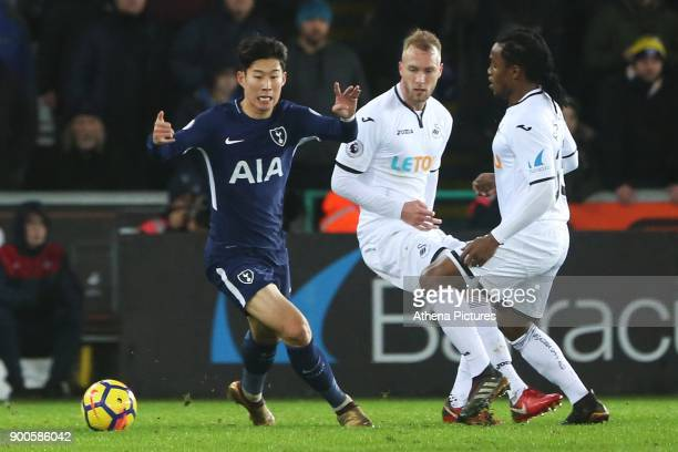 Son Heungmin of Tottenham Hotspur is challenged by Mike van der Hoorn and Renato Sanches of Swansea City during the Premier League match between...
