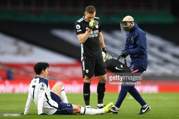Son Heung-Min of Tottenham Hotspur receives medical treatment as Bernd Leno of Arsenal looks on during the Premier League match between Arsenal and...