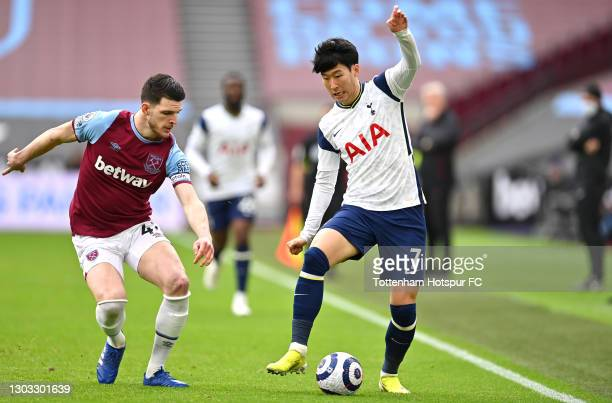 Son Heung-Min of Tottenham Hotspur runs with the ball whilst under pressure from Declan Rice of West Ham United during the Premier League match...