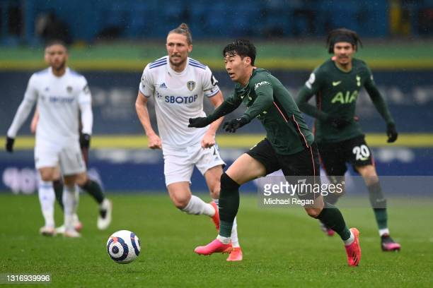 Son Heung-Min of Tottenham Hotspur runs with the ball whilst under pressure from Luke Ayling of Leeds United during the Premier League match between...